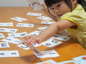 テーブルの上の英語のカードを取る女の子