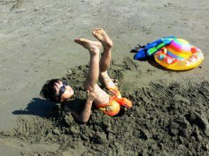 砂浜にひっくり返って遊ぶ水着姿の少年