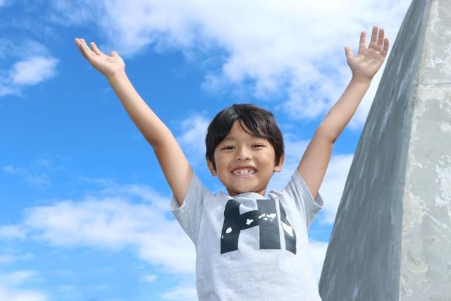 青空の下で両手を広げている少年