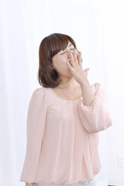 寝不足であくびをする女性