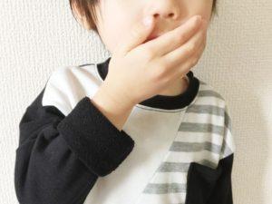 口に手を当てて咳をする子供