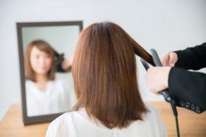 鏡の前で髪をセットしてもらう女性