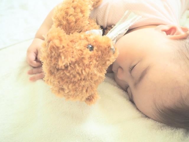 クマのぬいぐるみと寝る赤ちゃん